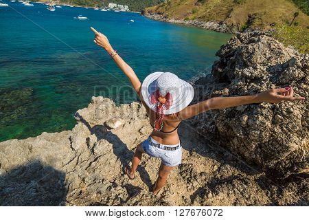 Happy and fashionable woman with shorts, suit and wide-brimmed hat enjoys the view from the rocky promontory. Spectacular little cove of Ya Nui Beach, Phuket, Thailand, Asia.