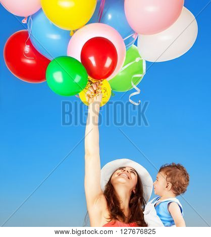 Portrait of a happy mother with little adorable son holding many colorful balloons over blue sky background, with pleasure playing outdoors, enjoying life