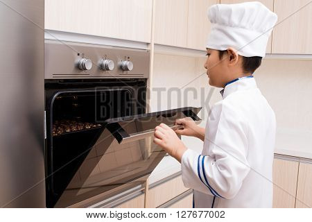 Asian Chinese Boy In White Chef Uniform Baking Cookies