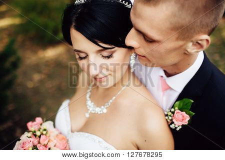 Beautiful bride and handsome groom at wedding day lovely hugging outdoors on nature. Bridal couple happy newlywed woman and man embracing in green park. Loving wedding couple outdoor. Close up.
