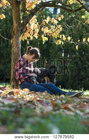 Young Caucasian woman sitting under an autumn tree cuddling her black dog.
