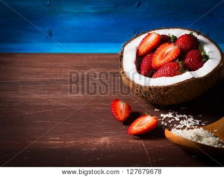 Half coconut with strawberries and shredded coconut on bright blue and brown wooden background with copy space