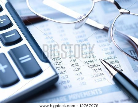 Close up view of calculator, pencil and glasses on newspaper