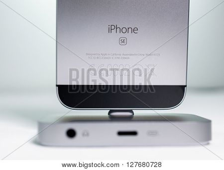 PARIS FRANCE - APR 21 2016: Front view of the new Apple iPhone SE in docking station combining the updated processor 4K rear camera touch id retina display