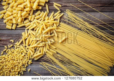 close up portrait of raw homemade italian pasta, macaroni, spaghetti, and fettuccine