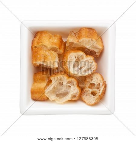 Sliced Chinese fried dough in a square bowl isolated on white background