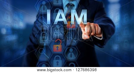 Security manager is pushing IAM on a touch screen interface. Information technology security concept for Identity and Access Management that is controlling access rights to data resources.