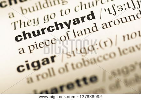 Close Up Of Old English Dictionary Page With Word Churchyard.
