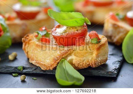 Delicious hot starters: Crispy baked crostini with tomato, mozzarella, olive oil and basil, served on a slate