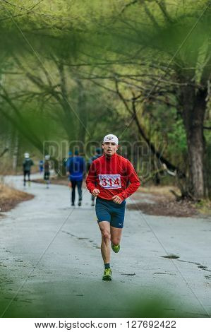 Chelyabinsk Russia - April 23 2016: young male runner athlete running in Park on way during Half marathon in woods