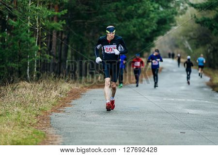 Chelyabinsk Russia - April 23 2016: runner middle-aged man running down road in Park during Half marathon in woods