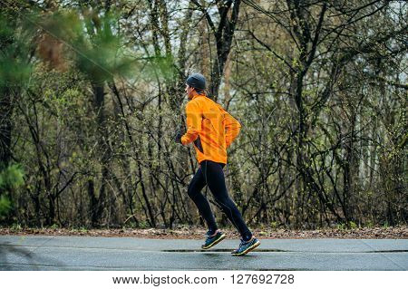 Chelyabinsk Russia - April 23 2016: man running down road in Park during Half marathon in woods