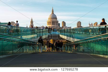 London England - April 20 2016 - St Paul's Cathedral and Millennium Bridge with tourists and locals walking with motion blur on a sunny afternoon