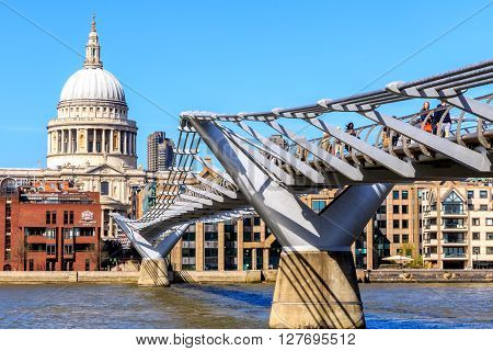 London England - April 20 2016 - St Paul's Cathedral and the Millennium Bridge with tourists and local people walking on a sunny and cloudless afternoon.