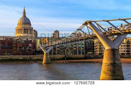 London, England - April 20, 2016 - St Paul's Cathedral and the Millennium Bridge with tourists and local people walking on a sunny afternoon.