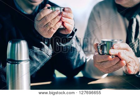 Close up of senior couple hands holding cups with hot coffee over a wooden table