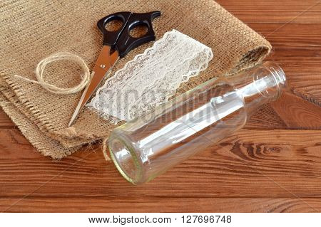 Glass bottle, scissors, burlap, cord, lace. Set for handmade vase. Rustic style. Diy concept. Brown wooden table