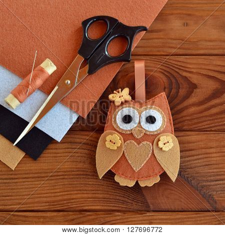 Felt brown owl. Shabby chic style. Scissors, felt sheets on a wooden table. How to make handmade toy