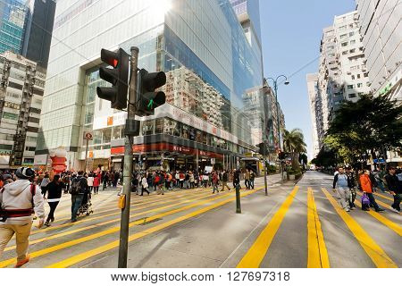 HONG KONG, CHINA - FEBRUARY 8, 2016: Crowd of people walking through the crossroad in bright light street with high modern stuctures on February 8, 2016. There are 1223 skyscrapers in Hong Kong.