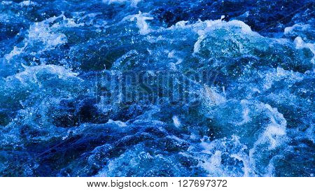 beautiful clear blue water flows boils and splashes splashing spray droplets and foam