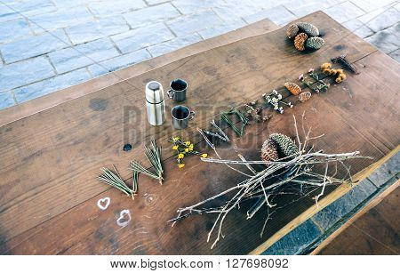 Wooden table with thermos, coffee cups and wanderlust word made with natural objects