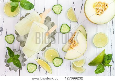 Refreshing mexican style ice pops - cucumber lime honeydew margarita paletas - popsicles. Top view overhead. Cinco de Mayo recipe
