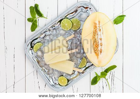 Refreshing ice pops over silver tray. Lime honeydew white sangria paletas - popsicles. Top view overhead