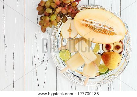 Refreshing ice pops over silver tray. Pear peach grape lime honeydew white sangria paletas - popsicles. Top view overhead copy space