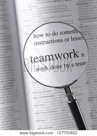 Magnifying Glass and dictionary Highlighting Teamwork text