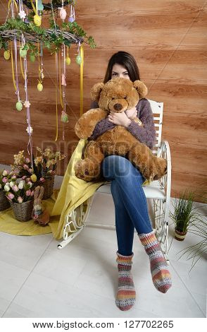 angry girl with a plush bear sitting on a chair