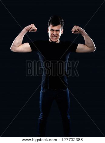 young man showing his muscles on a black background