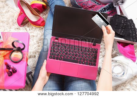 Trendy woman shopping online with a credit card and a laptop