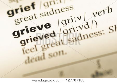 Close Up Of Old English Dictionary Page With Word Grieve.