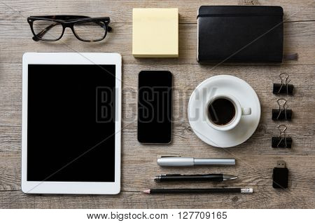 Top view of office desk with digital tablet, smart phone, supplies and coffe cup in wooden background. Businessman tidy desk with tablet and smartphone in black screen.