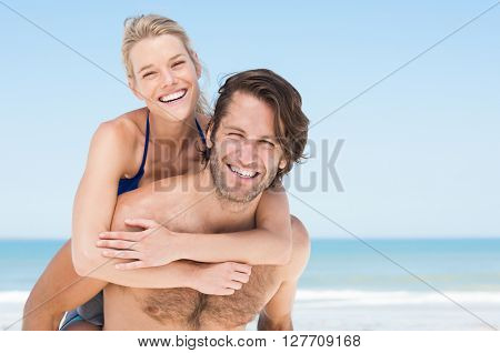 Happy man in love giving piggyback ride to smiling woman at the beach. Couple enjoying vacation at beach with copy space. Woman piggybacking on the back of her boyfriend.