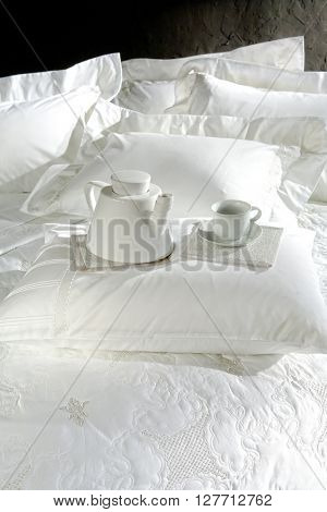 tea breakfast on bed closeup , classy white covers on black wall background