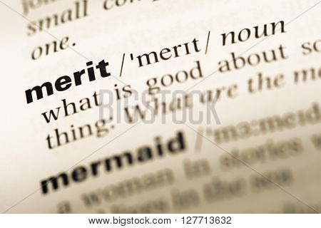 Close Up Of Old English Dictionary Page With Word Merit.