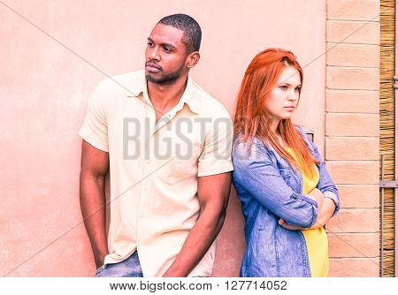 Serious couple back to back with love problems looking away - Mixed race friends in upset mood standing outside - Breakup of a relationship concept with feeling of sadness and anger - Focus on male