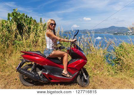 Young Slim Woman Riding Motorbike On A Sea Coast