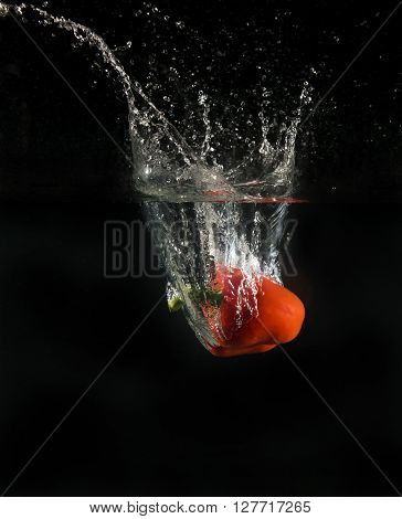 View of sweet pepper droping into water on black background.