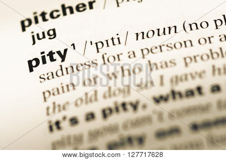 Close Up Of Old English Dictionary Page With Word Pity.
