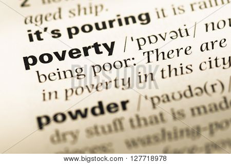 Close Up Of Old English Dictionary Page With Word Poverty.