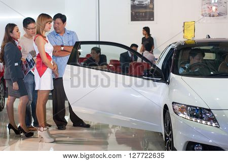 MAKASSAR, INDONESIA - CIRCA OCTOBER 2015. Indonesian female model look at a visitor who try Honda CR-Z seat at an automotive expo circa October 2015 in Makassar, Indonesia