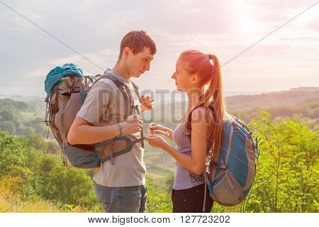 Girlfriend and Boyfriend Teenagers Couple with Backpacks on Green Forest Background Staying Talking Smiling rising Sun on Background