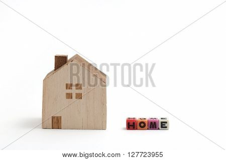 Miniature house with alphabet blocks that spell home on white background.