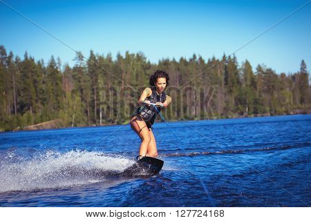 Woman study wakeboarding on a lake outdoors