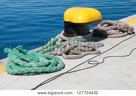 Yellow Mooring Bollard And Nautical Ropes