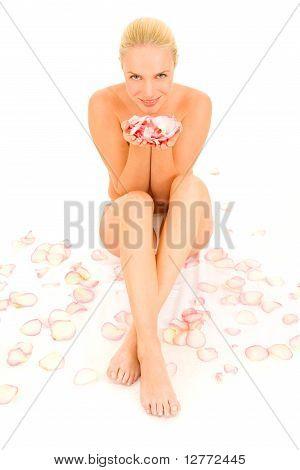nude woman sitting between rose petals