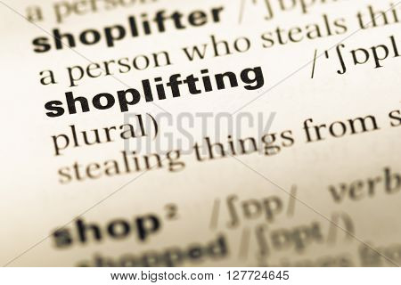 Close Up Of Old English Dictionary Page With Word Shoplifting.