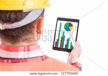 Modern builder or construction worker checking financial charts and statistics on wireless tablet